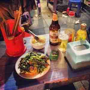 Street food like these noodles with beef and morning glory is one of Hanoi