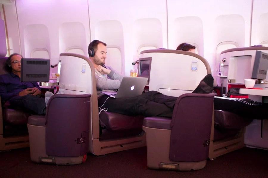 Passengers enjoying various personal entertainment.