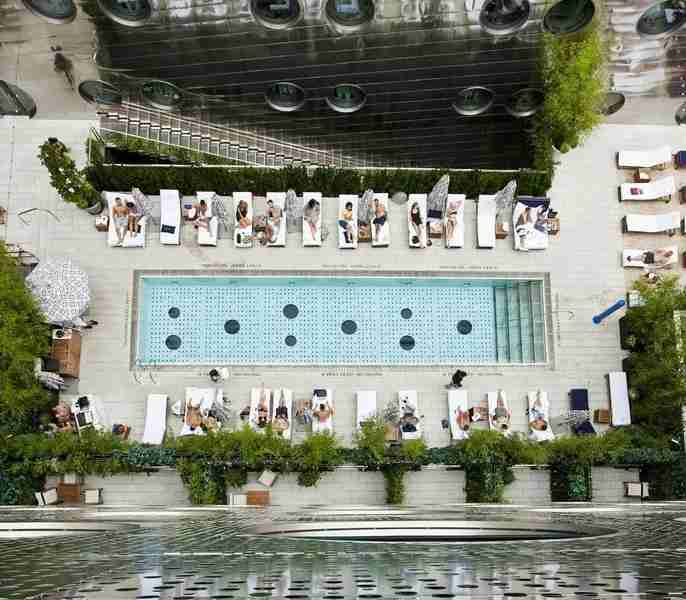 The Dream Hotel Downtown features imported sand and a glass-bottom pool.