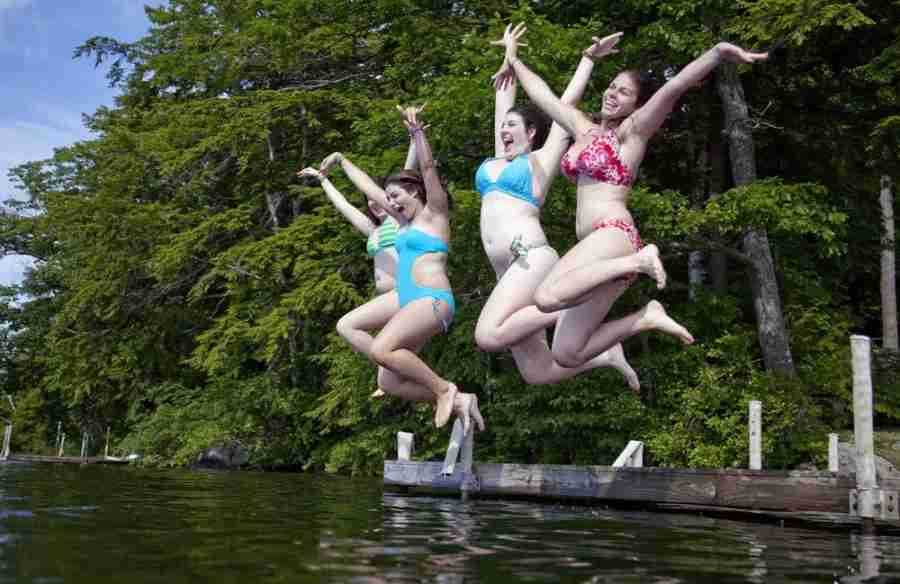 Teenagers — happy, smiling, joyful teenagers — jumping into Squam Lake. Photo courtesy of Shutterstock.