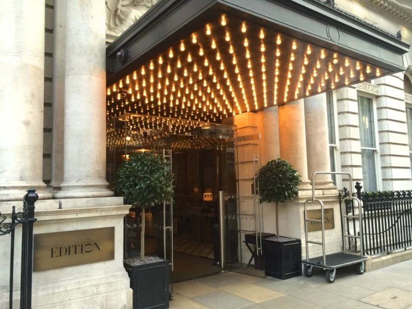 The London EDITION makes the most of its small entrance with a canopy of marquee lights.