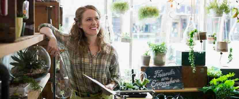 Smiling terrarium shop owner taking inventory with clipboard