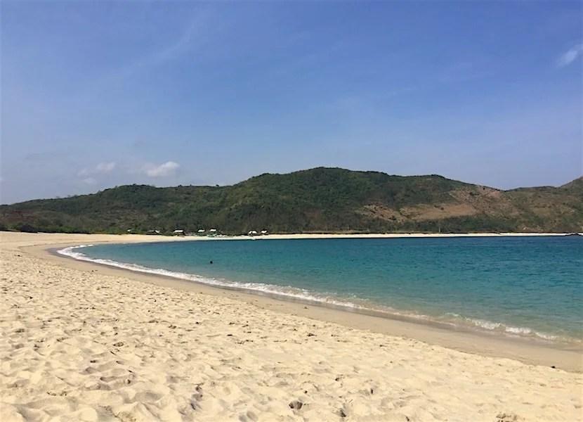 The bright blue bay at Mawun.
