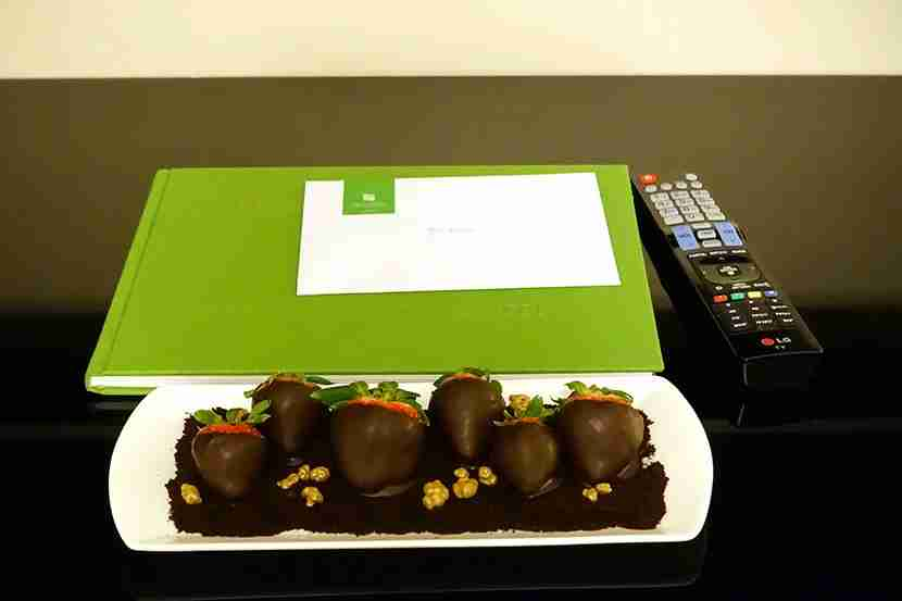 A welcome gift of chocolate-covered strawberries, set next to a book about the hotel