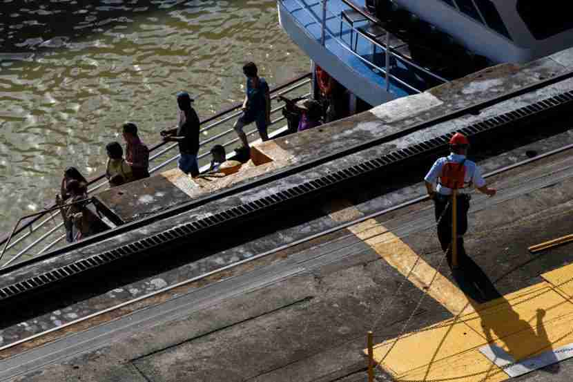 Tourists ride a boat through the Miraflores locks of the Panama Canal. As the water level decreased, they were almost hidden by the walls of the canal.