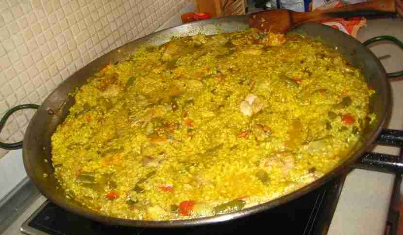 Paella, filled with rabbit and vegetables.