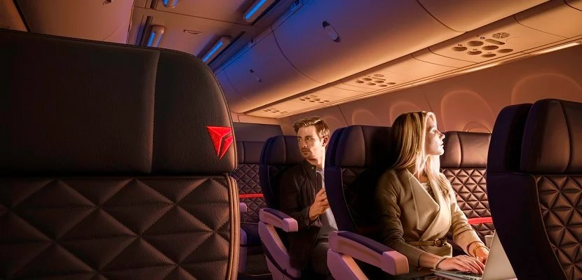 A woman using her laptop and and man in First Class on a Boeing 737-900ER (739). - These images are protected by copyright. Delta has acquired permission from the copyright owner to the use the images for specified purposes and in some cases for a limited time. If you have been authorized by Delta to do so, you may use these images to promote Delta, but only as part of Delta-approved marketing and advertising. Further distribution (including proving these images to third parties), reproduction, display, or other use is strictly prohibited.