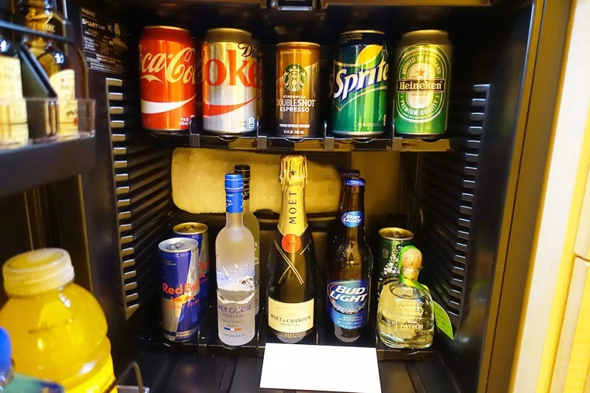 The mini-fridge was stocked with several hard and soft beverages available for purchase.