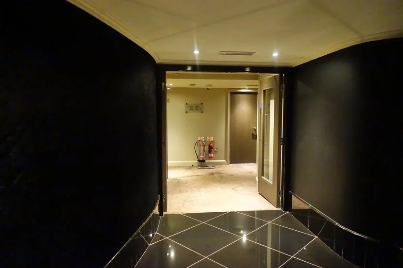 The chic black elevator area giving way to the cheesy pink carpeted hallways.