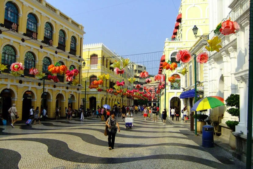 "Old Macau's Senado Square is full of fantastically-preserved Portuguese architecture. Image courtesy of <a href=""http://www.shutterstock.com/pic-158363639/stock-photo-macau-china-september-19-unidentified-tourists-walk-around-senado-square-on-september-19-2011-in-historic-center-of-macau-china-macaus-economy-is-heavily-dependent-on-tourism-and-g.html?src=Qbk7BmN1_aIESGOWBoyDCA-1-15"" target=""_blank"">Shutterstock</a>."
