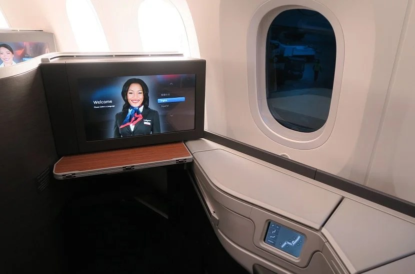 The in-flight entertainment screen and cubby containing the headphone jack and remote.