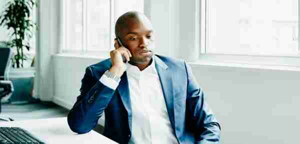 Frustrated businessman sitting at office workstation waiting while on smartphone