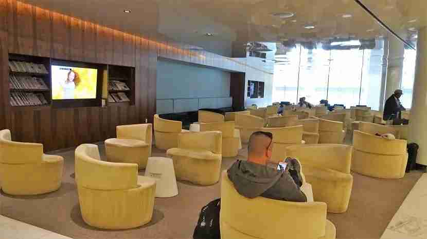 A large seating area with curvy furniture. On the left, TVs and periodicals.