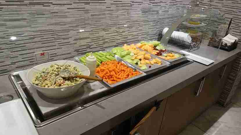 Cold and fresh, a nice selection of fruits and vegetables next to a huge bowl of pasta salad.