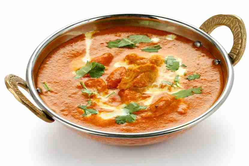 Rich and creamy butter chicken eaten with naan and onion salad. Image courtesy of Bonchan via Getty Images.