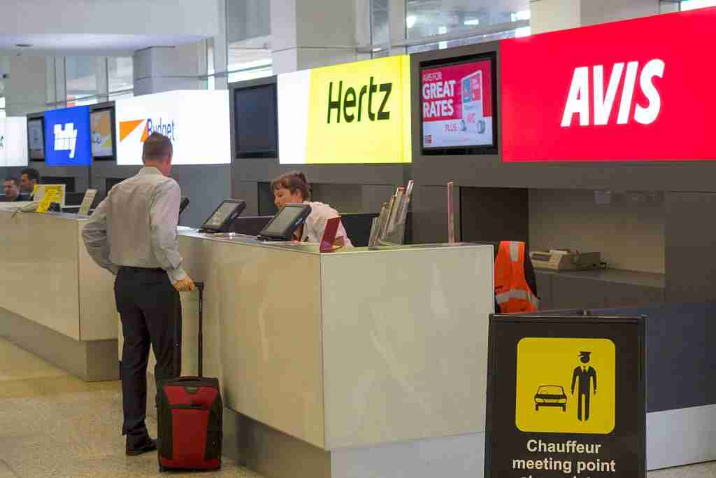 Australia, Victoria Melbourne Tullamarine International Airport MEL concourse terminal rental car competing businesses counter counters Avis Hertz Budget Thrifty man customer luggage. (Photo by: Jeff Greenberg/UIG via Getty Images)