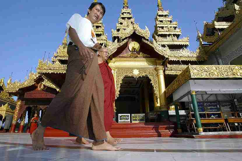 The Burmese national costume, a tunic and longyi — a piece of cloth wrapped around the waist and knotted in front — is everywhere, like here at the Shwedagon Pagoda. Image courtesy of Saeed Khan/Getty Images.
