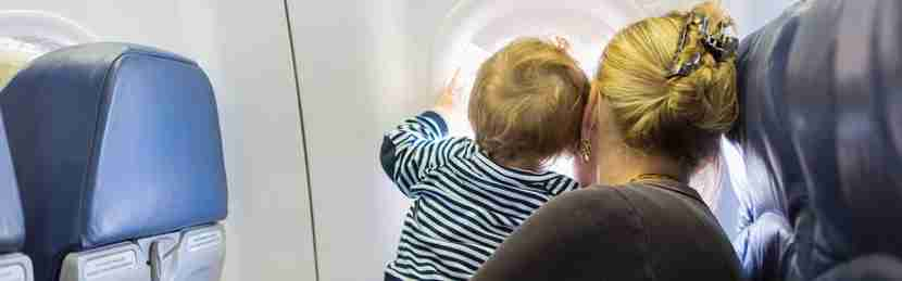 Mother and baby looking out airplane window
