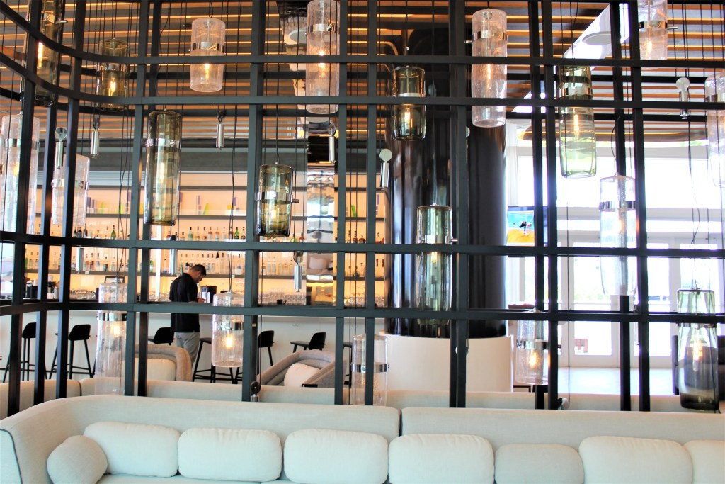 "The lobby or ""Living Room"" is expansive featuring floor to ceiling windows, posh seating areas and partial ocean views."