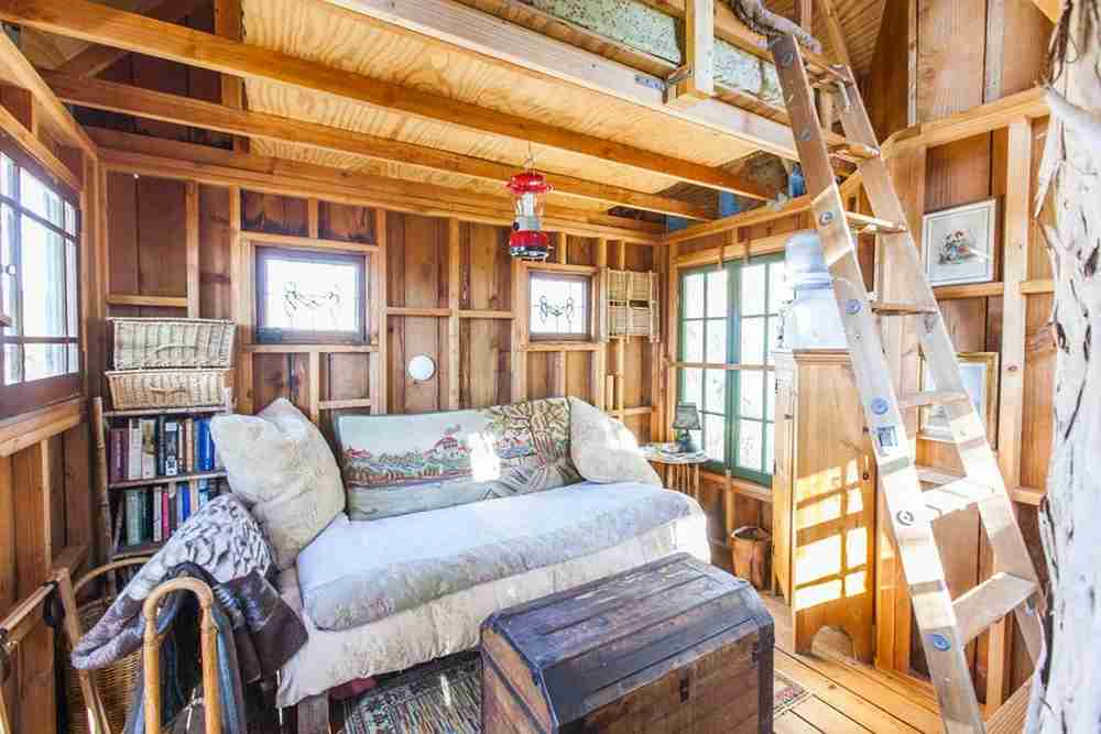 The living room has a small couch, while the bed is located in the loft. Image courtesy of Glamping Hub.