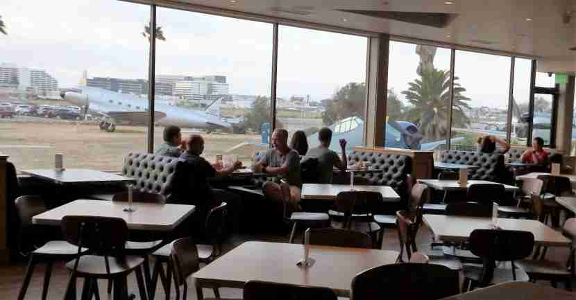 Enjoy your meal next to panoramic windows with views of vintage aircraft and LAX.