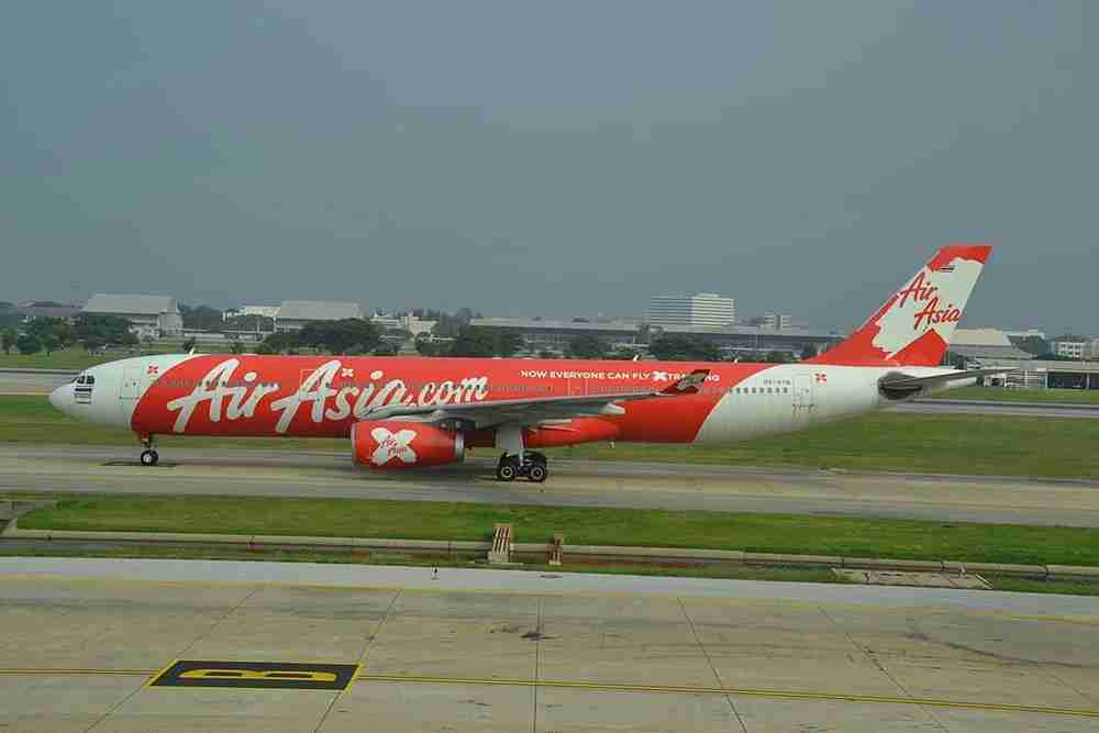 Can you spot the golfers behind the AirAsia plane? Image courtesy of Alec Wilson/Wikipedia.