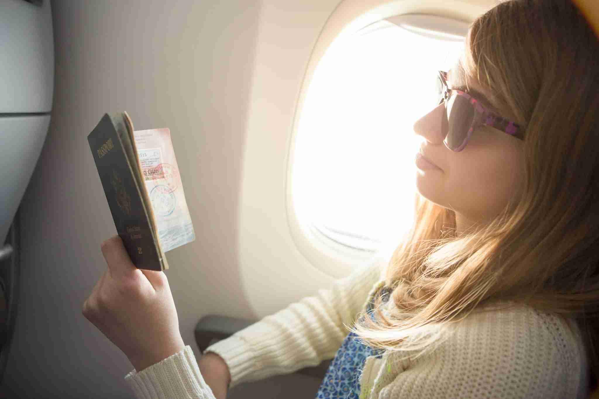 Tween girl looking at stamps on passport