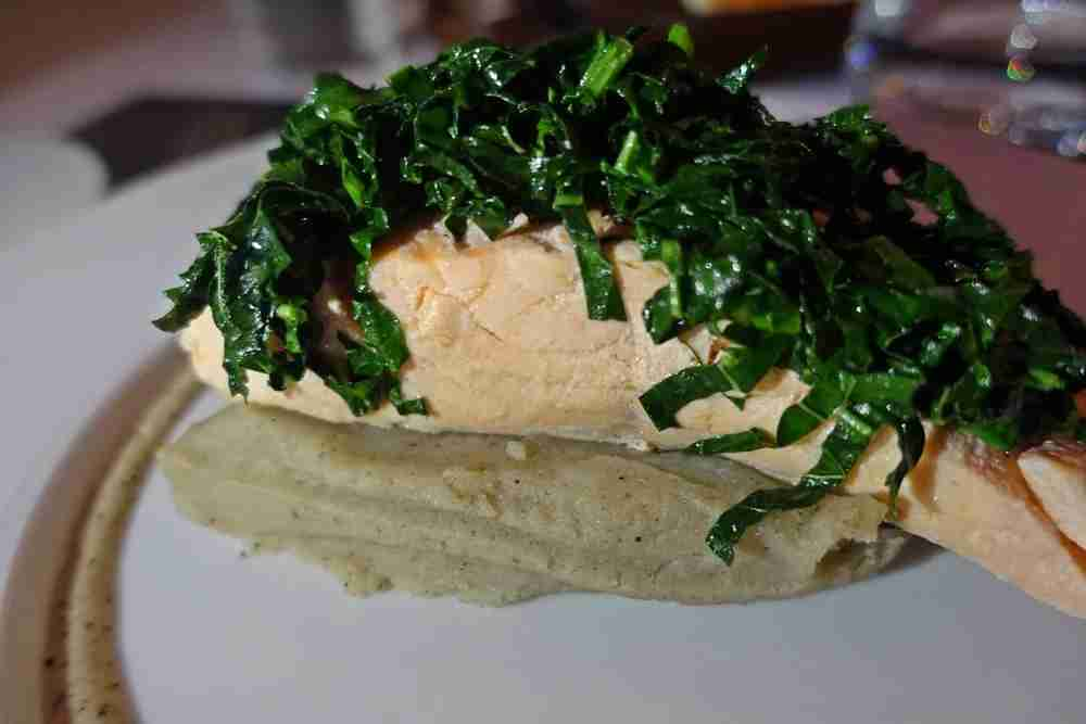 Salmon topped with kale over potatoes.
