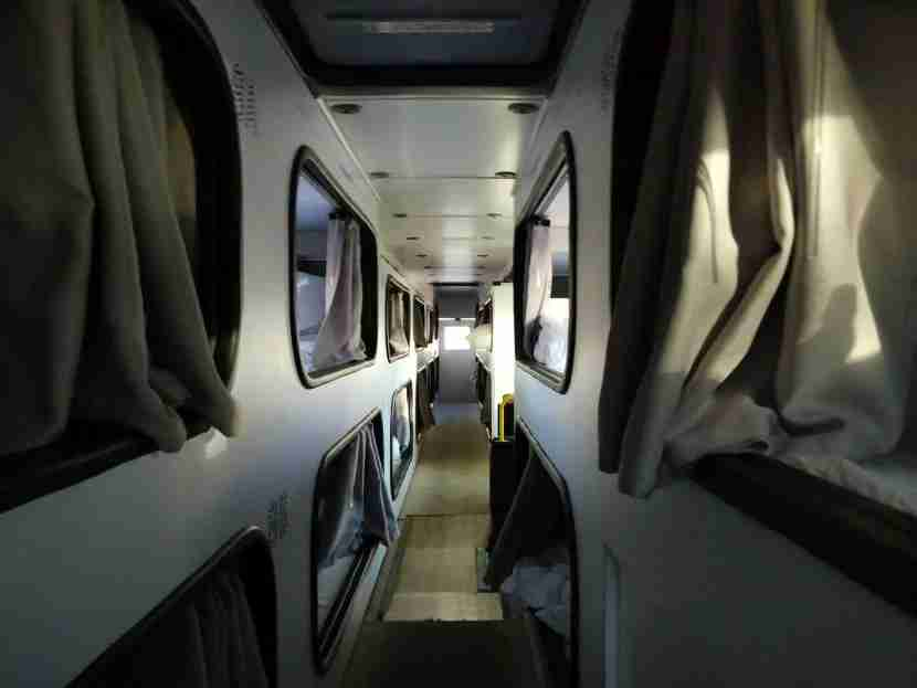 The hallway upstairs on the bus, with pods on each side.