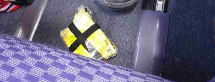 A lifejacket dangled from under the seat onto the floor.