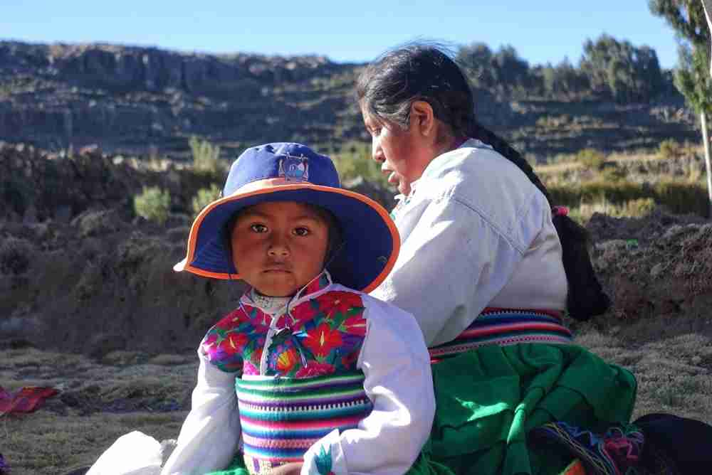 A mother weaves next to her inquisitive daughter in Amanpuri, an island in Lake Titicaca.