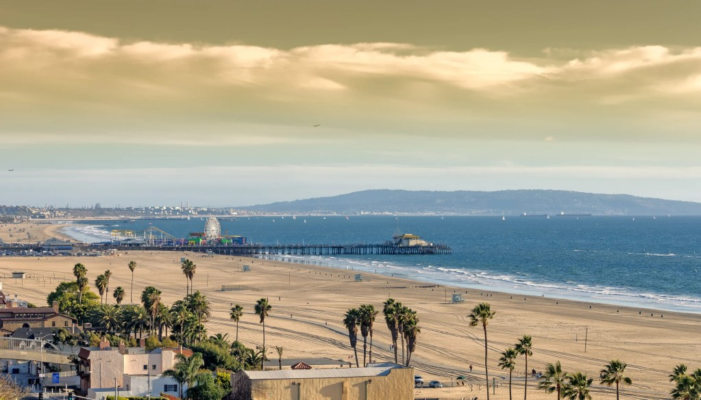 A serene view of the Pacific ocean at Santa Monica beach, with famous Santa Monica pier and popular amusement park.