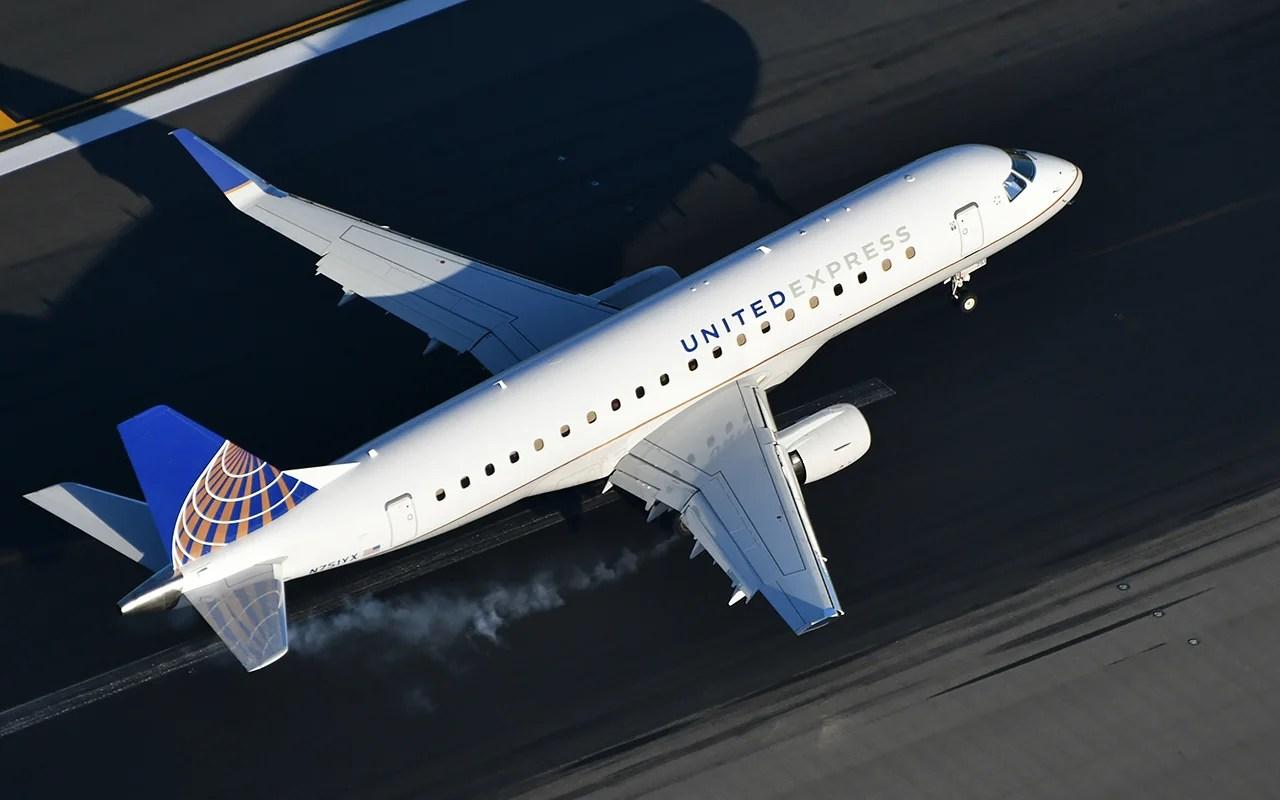 An Embrarer 175 regional jet burns some rubber on landing