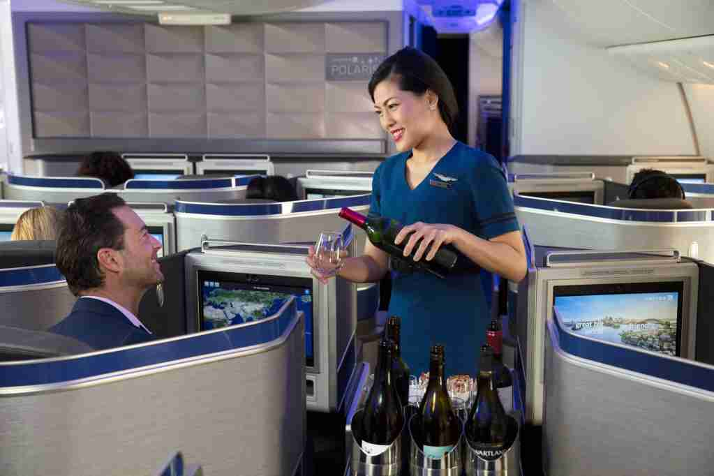 A United Airlines flight attendant serves wines in Polaris international business class. (Photo courtesy of United Airlines)