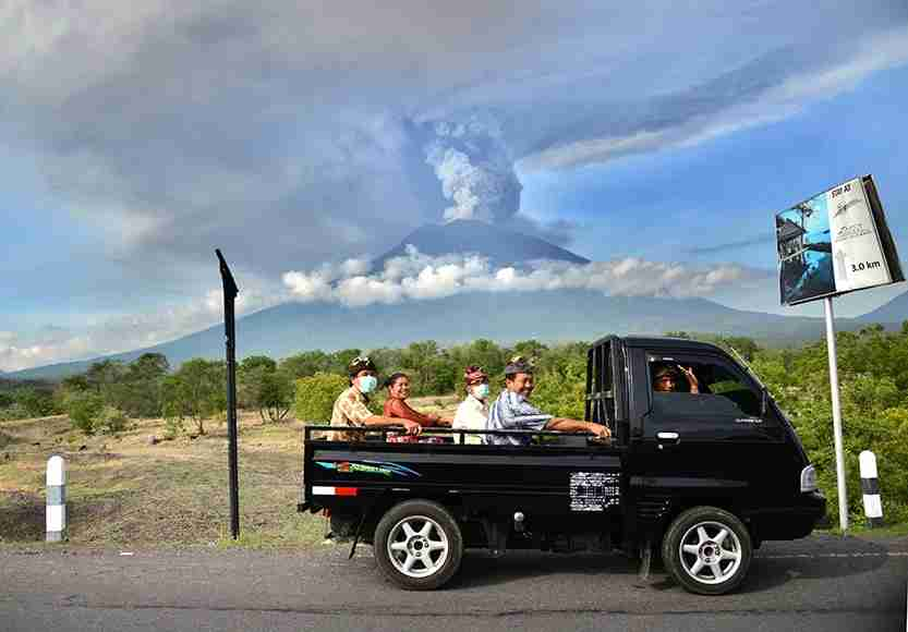Balinese people ride on an open car past Mount Agung erupting seen from Kubu sub-district in Karangasem Regency. Photo by SONNY TUMBELAKA/AFP/Getty Images