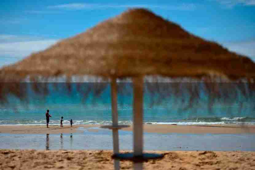 A man and two children stand on the beach in Praia da Luz in Algarve, southern Portugal, on April 28, 2017.Scarred by Madeleine McCann