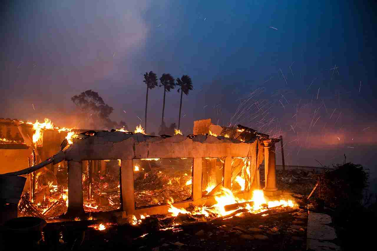 Remnants of a burned down a home as a brush fire continues to threaten other homes. (Photo by Marcus Yam / Los Angeles Times via Getty Images)
