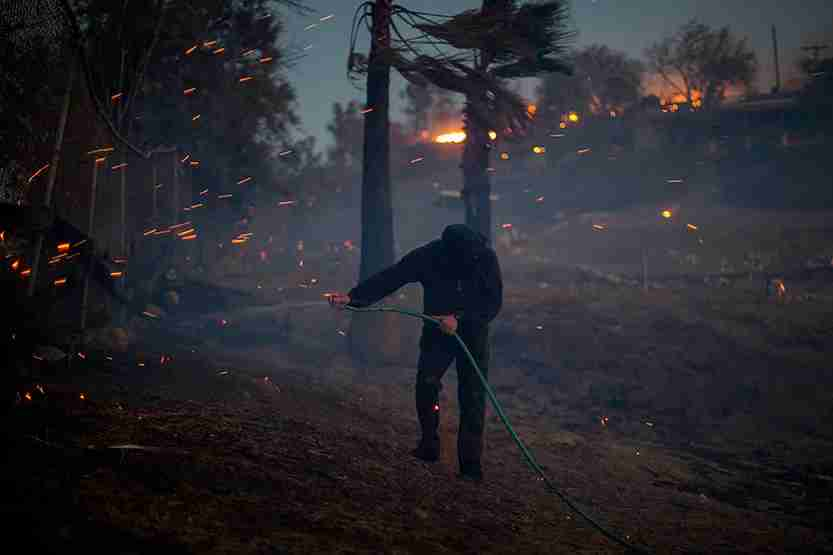 A strong wind blows embers around a resident hosing his burning property during the Creek Fire in Sunland, California. (Photo by David McNew/Getty Images)