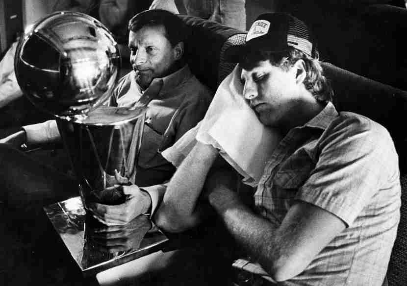 IN FLIGHT - MAY 15: Boston Celtics player Larry Bird, right, sleeps on the plane back to Boston from Houston, as Celtics trainer Ray Melchiorre, left, holds the NBA Championship trophy on May 15, 1981. The Celtics beat the Houston Rockets 102 - 91, in the final game of the 1981 NBA Championships. (Photo by Frank O