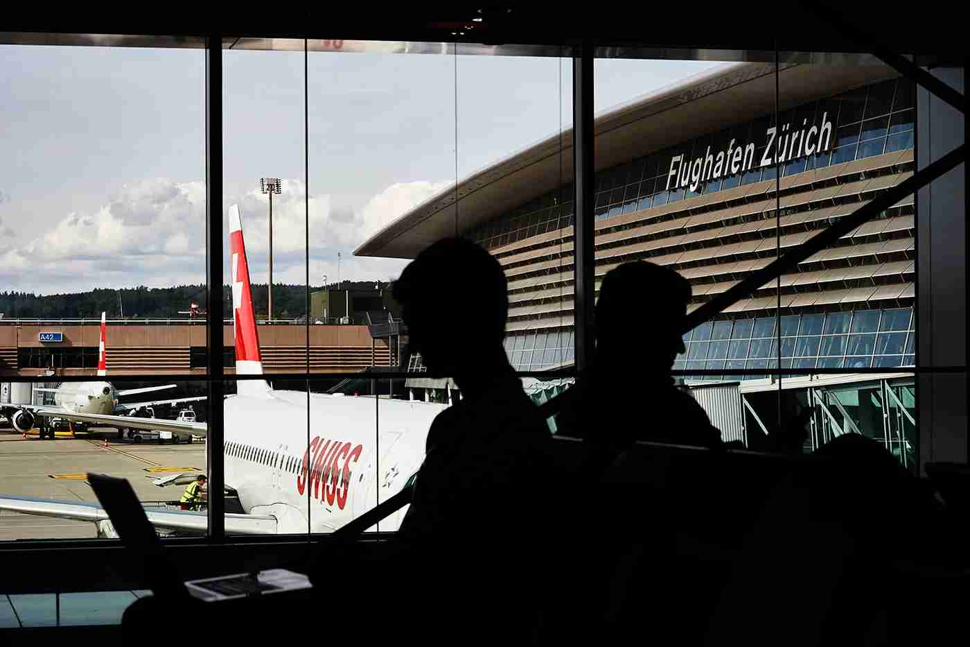 Passengers sit in front of an aircraft of Swiss International Airlines on July 6, 2016 at the Zurich Airport in Zurich. / AFP / MICHAEL BUHOLZER (Photo credit should read MICHAEL BUHOLZER/AFP/Getty Images)