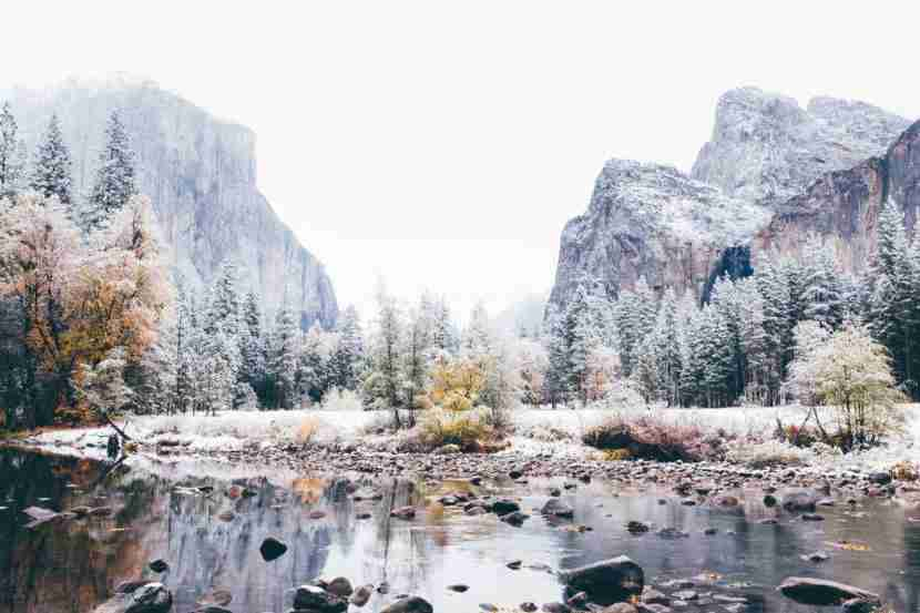 A landscape image of Yosemite valley with the Merced River in the foreground and El Capitan and Bridalveil Falls in the background. This was taken on the day when Yosemite was dusted with snow, on the cusp of winter while the trees still had the last of the autumn colors. Photo by Benjeev Rendhava // Getty Images