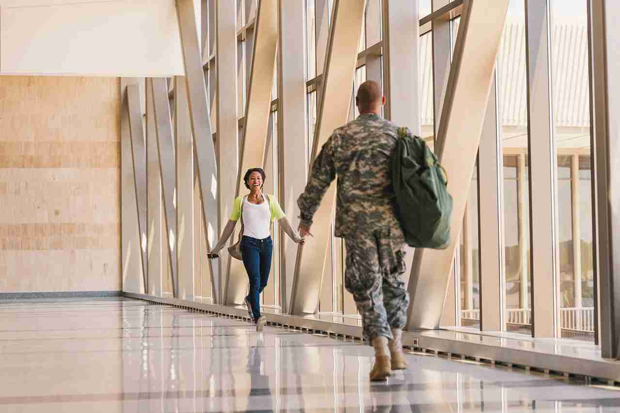 Returning soldier greeting girlfriend in airport. (Photo by Mark Edward Atkinson/Tracey Lee/Getty Images)