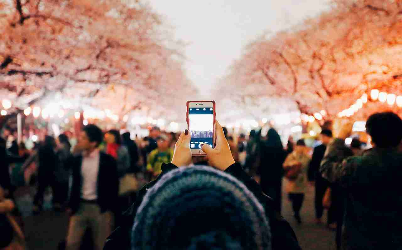 A woman uses a smartphone to take a photograph of cherry blossoms at night on April 1, 2016 in Tokyo, Japan. (Photo by Tomohiro Ohsumi/Getty Images)