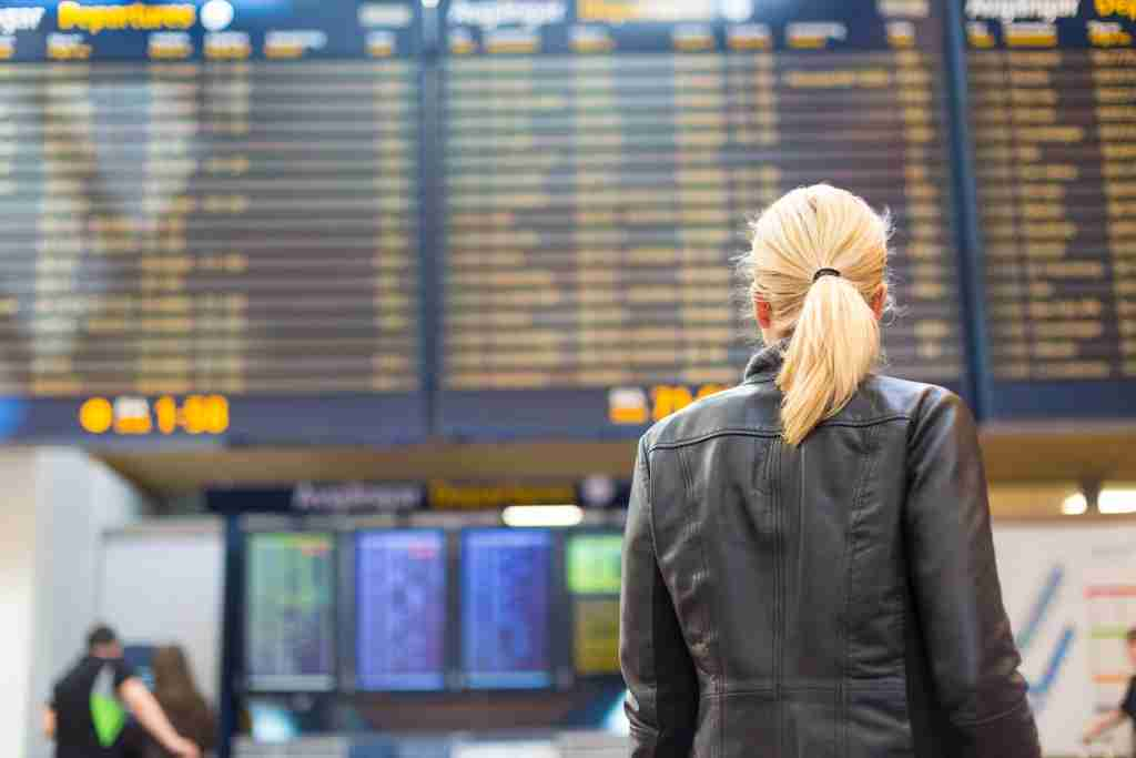 Casually dressed young stylish female traveller checking a departures board at the airport terminal hall in front of check in couters. Flight schedule display blured in the background. Focus on woman.