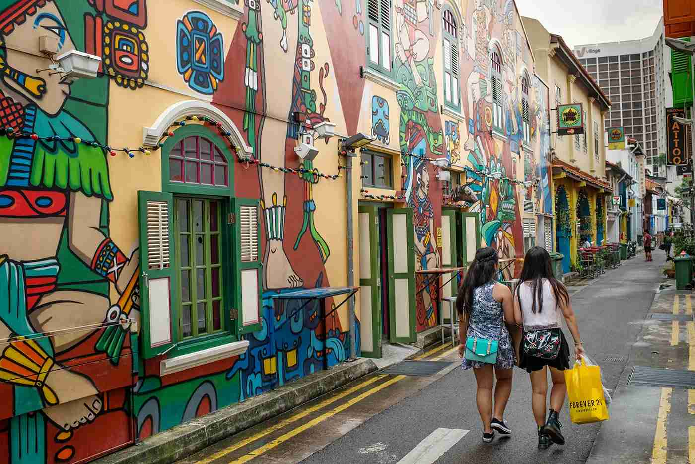 SINGAPORE - 2013/11/28: Two young women walk pass a colourful building located in a shopping and leisure district that has proper graffiti style paintings on it. (Photo by Jonas Gratzer/LightRocket via Getty Images)