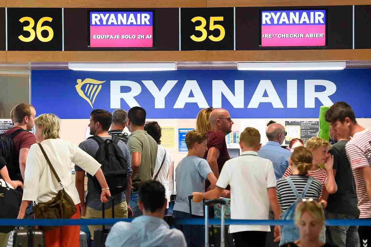Passengers queue at Ryanair check-in counters at the airport in Valencia on July 25, 2018 as the airline