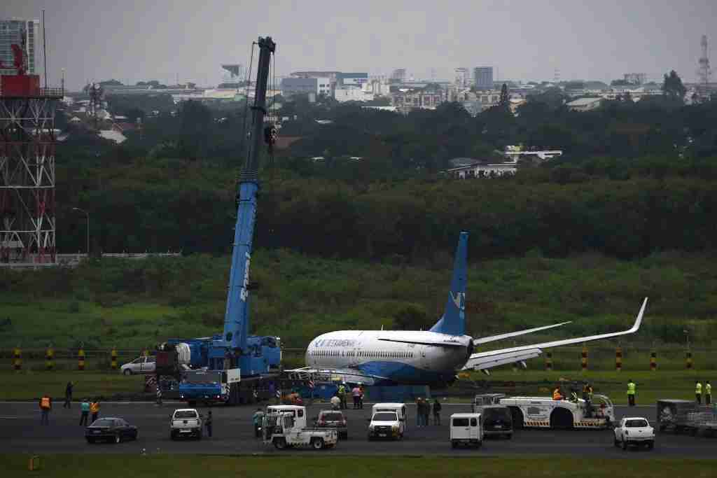 A crane prepares to lift a Xiamen Air Boeing 737-800 series passenger aircraft, operating as flight MF8667 from Xiamen to Manila, after it skidded off the runway while attempting to land in bad weather at the Manila international airport on August 17, 2018. - The Chinese passenger jet slid off the runway as it landed at Manila airport in torrential rain, authorities said on August 17, with all 165 people on board safely evacuated. (Photo by Ted ALJIBE / AFP) (Photo credit should read TED ALJIBE/AFP/Getty Images)