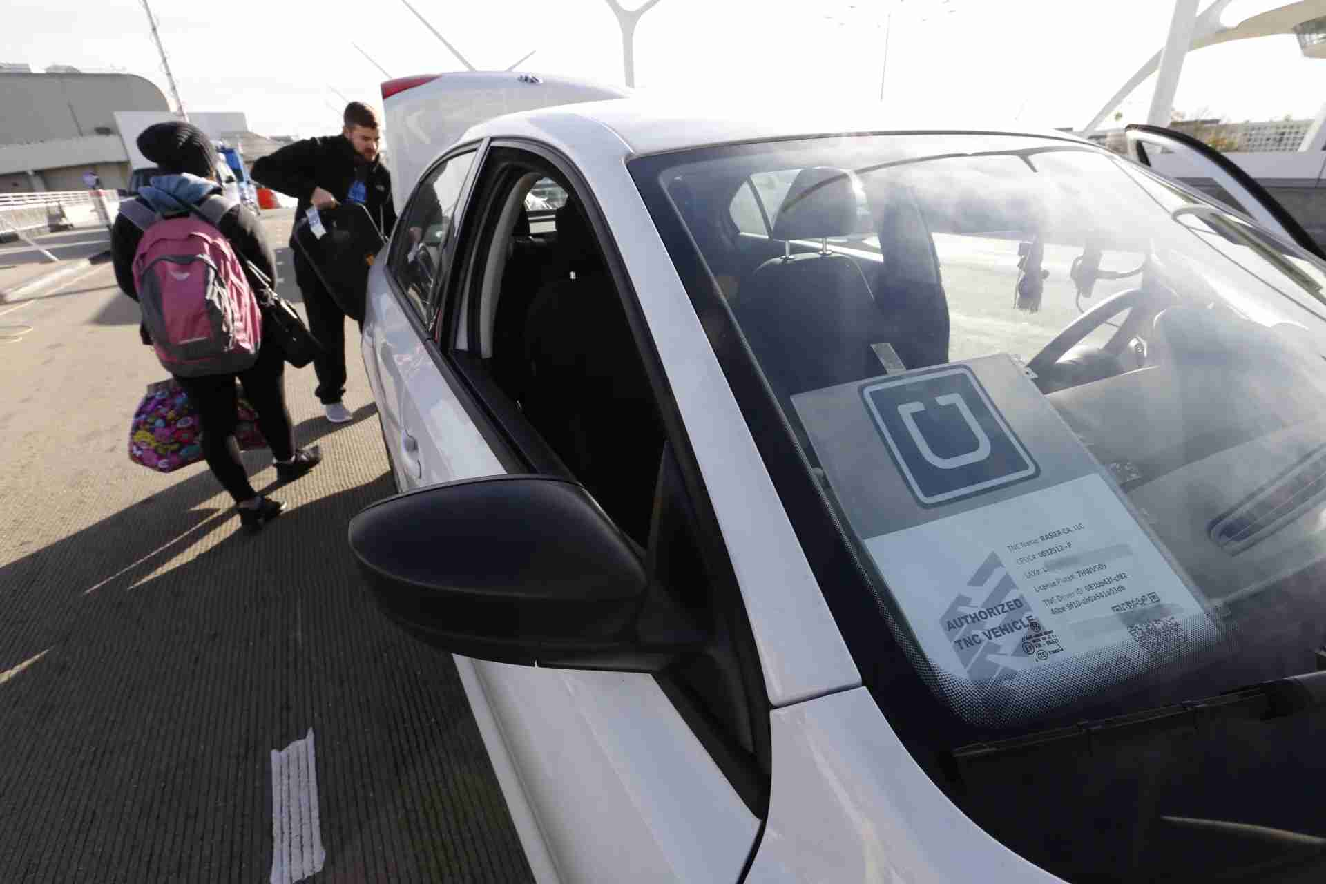 LOS ANGELES, CA - JANUARY 21: Kevin Bonsignore and Danni Clay from Kansas City catch their UberX ride as UberX begins making passenger pickups at Los Angeles International Airport on January 21, 2016 in Los Angeles, California. UberX joins competing service Lyft as the only such services offering pickups at LAX. (Photo by Al Seib / Los Angeles Times via Getty Images)