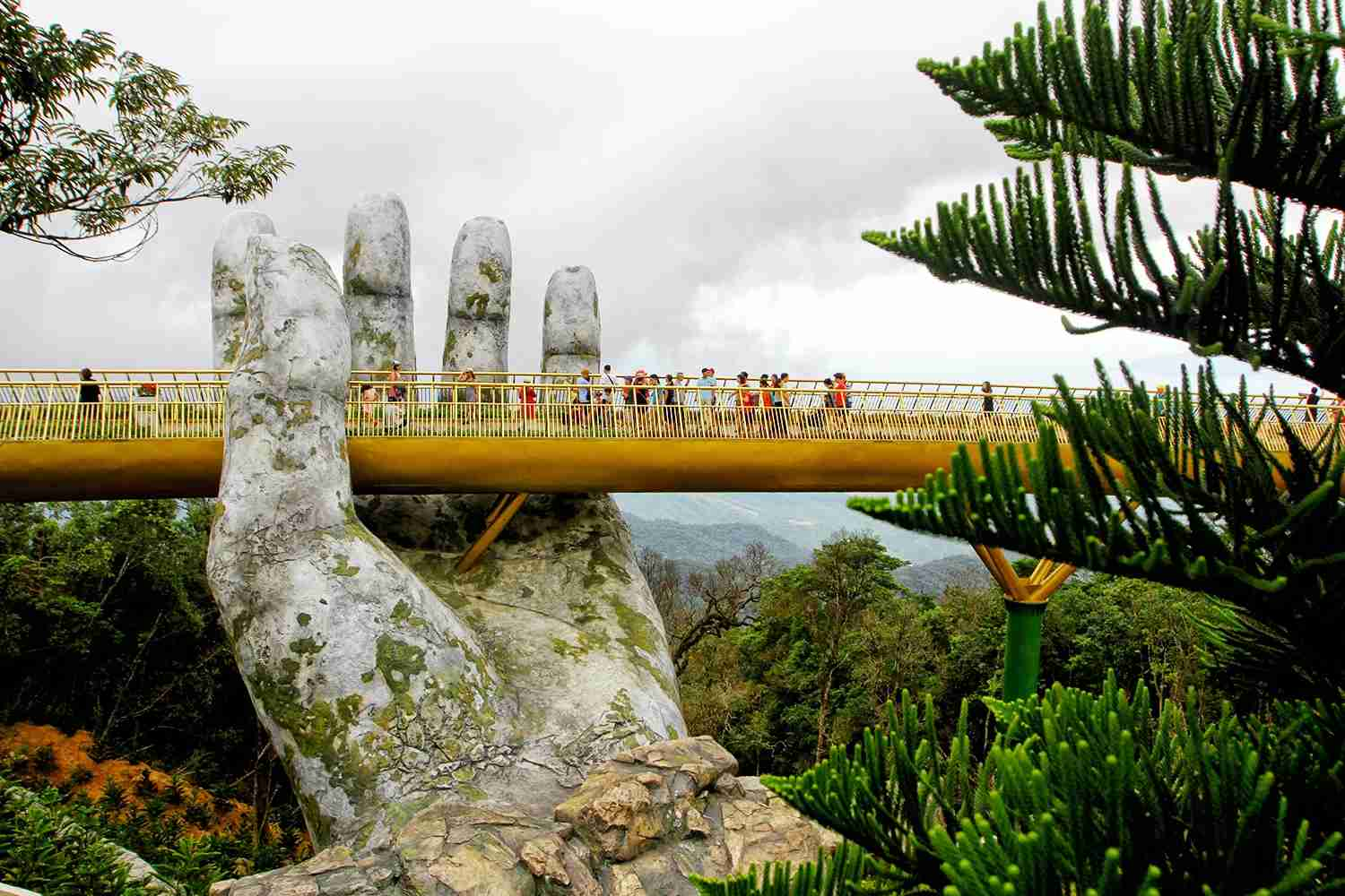 "In this photograph taken on July 31, 2018, visitors walk along the 150-meter long Cau Vang ""Golden Bridge"" in the Ba Na Hills near Danang. - Nestled in the forested hills of central Vietnam two giant concrete hands emerge from the trees, holding up a glimmering golden bridge crowded with gleeful visitors taking selfies at the country"