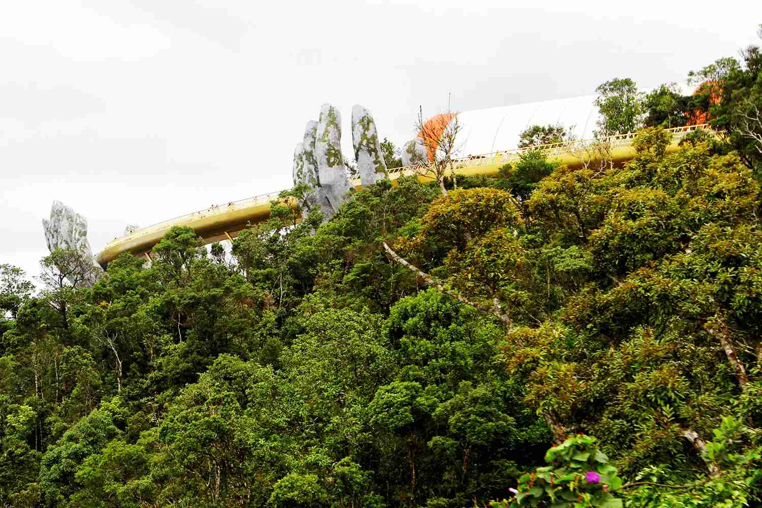 "In this photograph taken on July 31, 2018, the 150-meter long Cau Vang ""Golden Bridge"" is seen past hillside vegetation in the Ba Na Hills near Danang. - Nestled in the forested hills of central Vietnam two giant concrete hands emerge from the trees, holding up a glimmering golden bridge crowded with gleeful visitors taking selfies at the country"